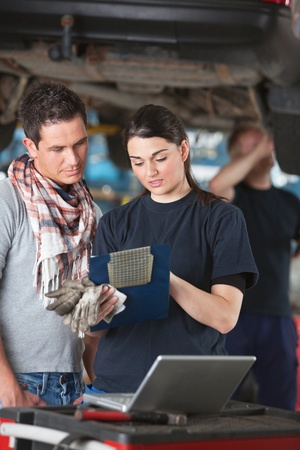 Female mechanic explaining cost to the client standing next to her with person in background photo