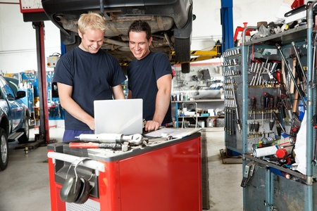 automobile workshop: Mechanics working on laptop in auto repair shop