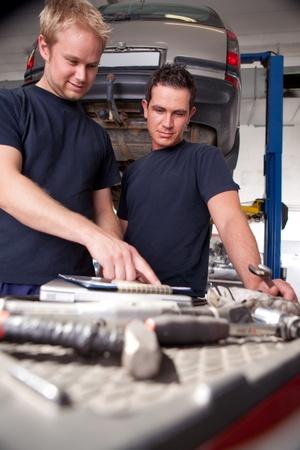 hombres trabajando: Dos mec�nicos mirando a la orden de trabajo y discusi�n de las reparaciones