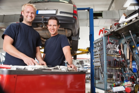 two car garage: Two happy mechanics standing in garage
