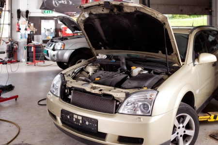 auto repair: A car in a professional auto repair shop with hood up