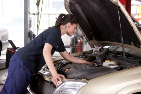 An attractive woman mechanic working on a car in a repair shop