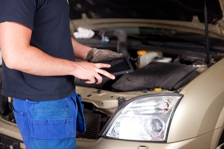 diagnostics: Detail of a mechanic with a digital tablet, car in background Stock Photo