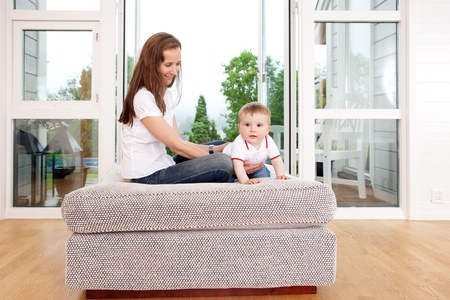 large windows: A young mother playing with happy son in beautiful living room interior. Stock Photo