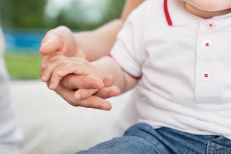 child's: Close-up of mother holding childs hand Stock Photo