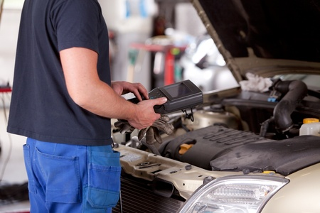 automobile workshop: Detail of a mechanic using electrnoic diagnostic equipment to tune a car Stock Photo