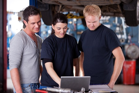 car hoist: A group of mechanics referring to a laptop for service order or diagnostics results
