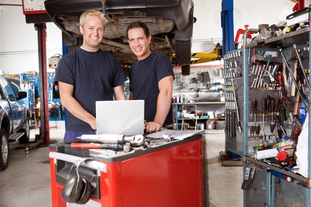 laptop repair: Portrait of mechanics with laptop in auto repair shop