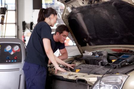 mecanico automotriz: Un hombre y una mujer que trabaja en mecánica de un coche en un taller de reparación de automóviles Foto de archivo
