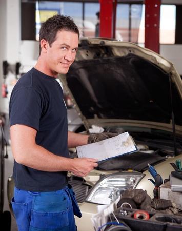 garage automobile: Portrait d'un mécanicien, en regardant la caméra avec un rapport de service dans la main