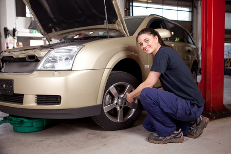 Beautiful female mechanic changing tire on car photo