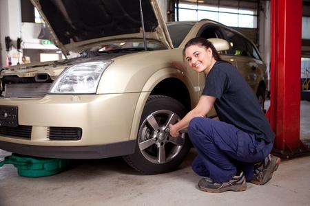 garage automobile: Mécanicien féminin beau changer pneu de voiture
