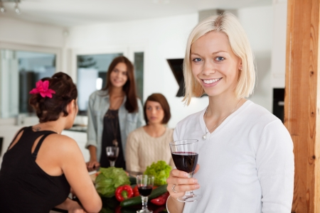 home party: Smiling woman holding glass at party with female friends in background Stock Photo