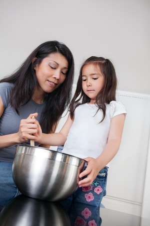 Mother and cute little daughter preparing cookies in kitchen photo