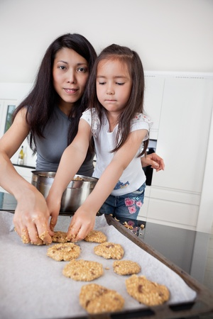 Portrait of mother and child in kitchen making cookies photo
