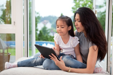 Cute little girl sitting with her mother on couch using a digital tablet. photo