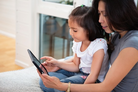 Mother and daughter reading electronic book at home photo