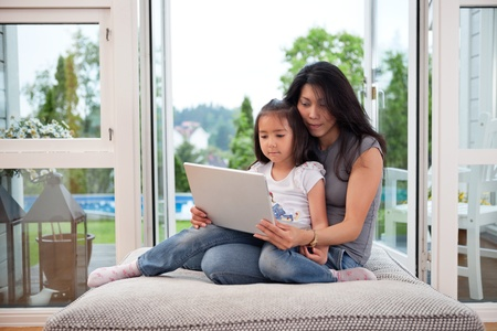 Cute daughter sitting on her mother's lap with laptop photo