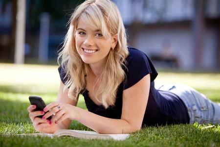 Happy university student sending a text message Stock Photo - 10559824