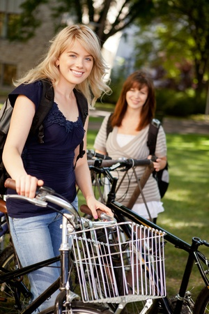 Two young female students with bikes on a university campus photo