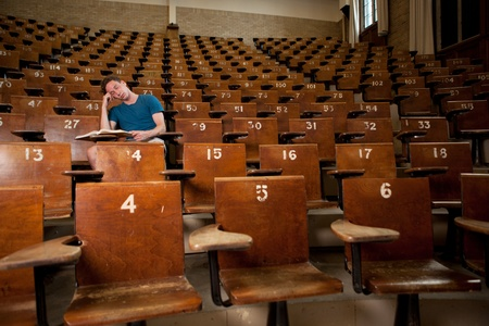 attend: Male university student asleep in a large lecture hall Stock Photo