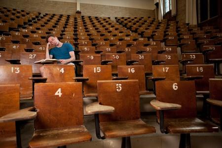 Maschio studente universitario addormentato in una sala conferenze di grandi dimensioni