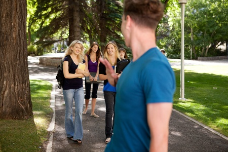 Male student waving to a group of female students Stock Photo - 10559807
