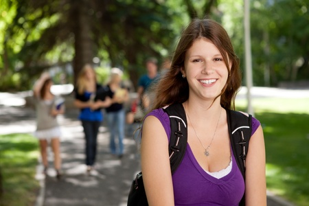 high schools: Portrait of a happy young college girl with friends in background