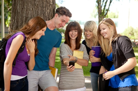 Group of students outdoors looking at a humorous image on a cell phone Stock Photo - 10559790