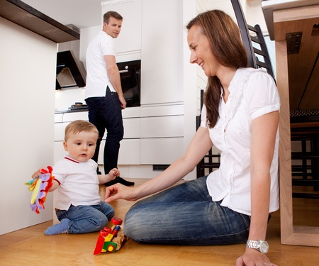 crawl: Mother playing with son on kitchen floor with father in background