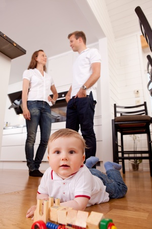 A happy child playing on kitchen floor with parents talking in the background photo