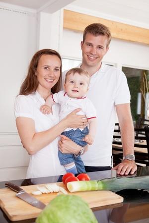 faire l amour: Portrait d'une famille heureuse jeune à la maison dans la cuisine