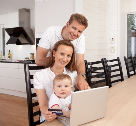 Happy family looking at the camera with a smile making an online purchase photo