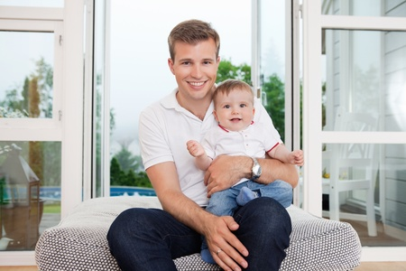 Portrait of smiling young father with child sitting on couch photo