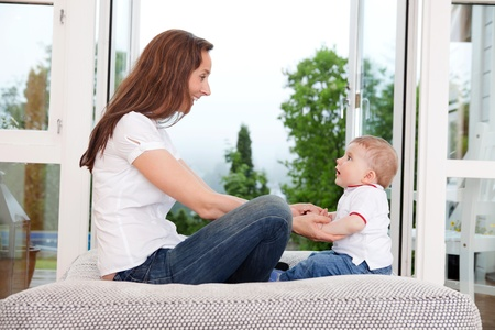 Young mother sitting on couch and looking at innocent child photo