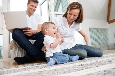 Smiling mother playing with cute child with man using laptop in background photo