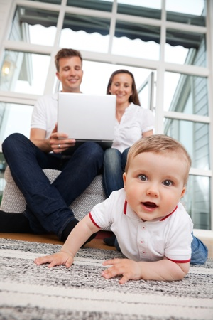 Portrait of cute child with parents using laptop in the background photo