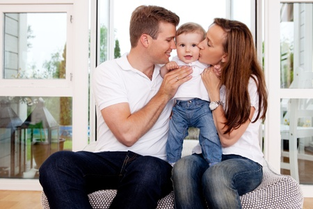 child couple: Mother and father hugging and kissing son in home interior Stock Photo