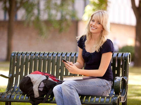 university text: Friendly young female student sitting on a bench sending a text message