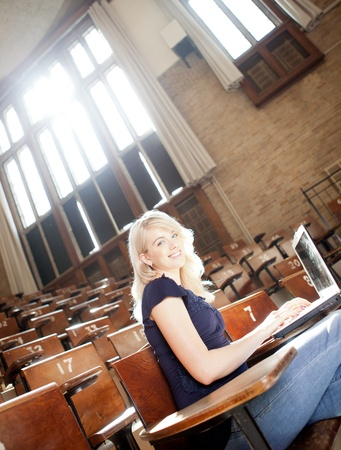 girl sit: Portrait of a young college girl in a lecture hall with laptop Stock Photo