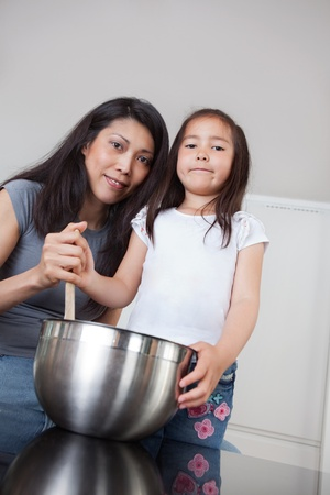 Portrait of smiling mother and cute little daughter in kitchen photo