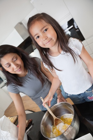 Woman and child preparing dough in kitchen photo