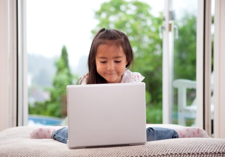 Young cute child using a computer in an indoor living room setting with large window photo