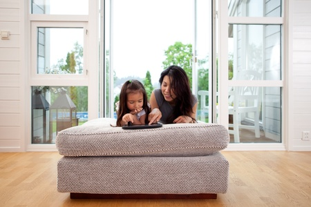 Mother and young daughter using a digital tablet in a living room interior photo