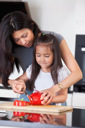 Little girl cutting pepper with the help of her mother photo