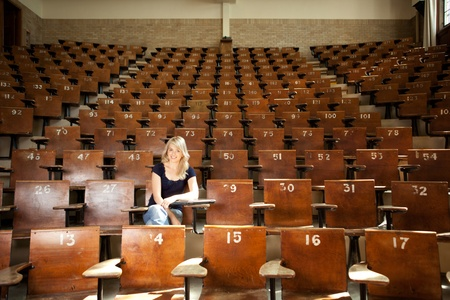 lecture theatre: Happy blond college student alone in large lecture hall