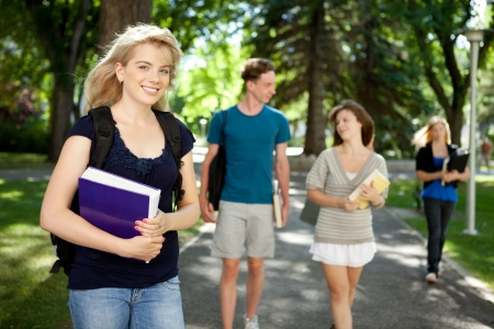school campus: Pretty blond college girl looking at camera with friends in background