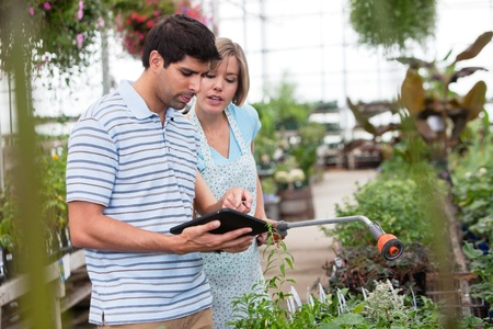 Customer using a digital tablet in greenhouse Stock Photo - 10679404