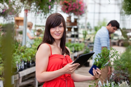 Beautiful woman holding tablet pc and potted plant with people in background photo