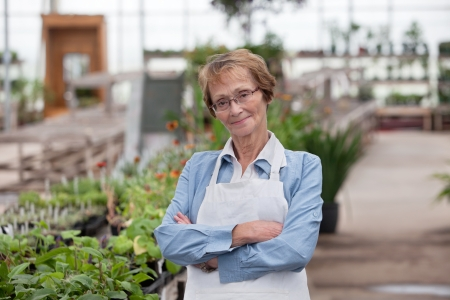 Portrait of smiling senior female worker standing with arms crossed photo